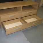 šviesiai ruda 4 įleistais stalčiais ir storintu korpusu svetainės komoda