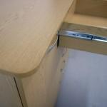 šviesiai rudos miegamojo komodos užapvalintas stalviršis ir pilnai ištrauktas stalčius