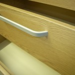 šviesiai rudos penkių stalčių miegamojo komodos lenkta pailga rankena