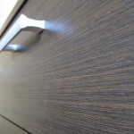 3 ilgų ir 2 trumpų stalčių tamsiai rudos virtuvės komodos tekstūra ir rankenėles