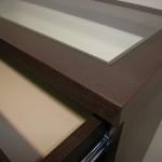 4 stalčių miegamojo komodos storinto stalviršio kampas ir įstiklintas veidrodis