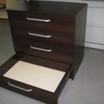 4 stalčių tamsiai rudos biuro komodos pilnai atidarytas apatinis stalčius