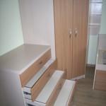 4 stalčių vaikų kambario komoda prie vaikų kambario spintos