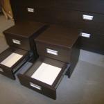 dvi tamsiai rudos dviejų stalčių miegamojo komodos pilnai atvertais stalčiais