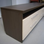 keturių stalčių tamsiai rudos spalvos svetainės komoda su balkšvos spalvos stalčiais