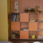 keturiomis oranžinės spalvos durelėmis ir atviromis lentynomis vaikų komoda