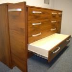 miegamojo kambario komodos atviros kairios durelės ir apatinis stalčius ištrauktas iki galo
