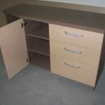 miegamojo komoda su durimis per vidurį ir trimis lentynomis už komodos durų