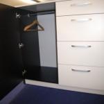 miegamojo komodoje pakaba rūbams už kairėje pusėje atvertų juodų komodos durelių