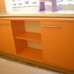 oranžinės spalvos komoda vaikams su dviem durelėmis šonuose ir dviem lentynomis per vidurį