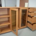 pravertos kairiosios svetainės komodos durelės su stiklu bei praverti ketveri stalčiai