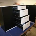 prieškambario komodos balti stalčiai su kokybiškais bėgeliais ir praviros dešinės juodos durelės