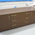 ruda ilga žema miegamojo komoda su 2 durelėmis ir 3 stalčiais per vidurį