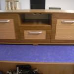 ruda svetainės komoda su atvira lentyna komodos viduryje ir dviem skylėmis laidams pravesti