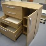 ruda svetainės komoda su giliu apatiniu stalčiumi ir pravertomis durelėmis