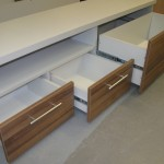 svetainės komodos atvira lentyna ir trys atidaryti stalčiai