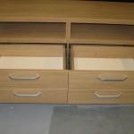 visi 4 pilnai atidaryti šviesiai rudos svetainės komodos stalčiai