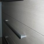šviesiai pilkos raštuotos akcijinės virtuvės komodos stalčiai ir tekstūra
