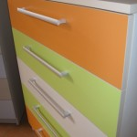 5 stalčių akcijinė komoda oranžiniais, žaliais ir baltu stalčiais
