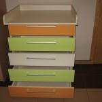 atverti oranžiniai žali ir baltas vystymo komodos stalčiai