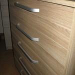 penkių stalčių rudos spalvos dryžuotu raštu akcijinė komoda iš arčiau