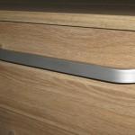 penkių stalčių rudos spalvos dryžuotu raštu akcijinės komodos rankenėlė iš arčiau