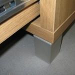 sidabrinės spalvos keturkampė televizoriaus komodos kojelė ir storintas komodos korpusas
