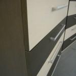 tamsiai ruda keturių stalčių akcijinė prieškambario komoda su dviem baltais stalčiais iš arti