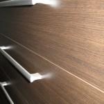 tamsiai rudos penkerių stalčių akcijinės prieškambario komodos raštas iš arti