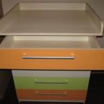 trispalvės vystymo komodos atvertas oranžinis stalčius