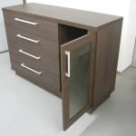 tamsiai rudos spalvos 4 stalčių komodos atvertos įstiklintos durelės