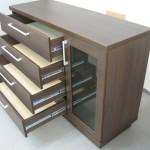 tamsiai rudos spalvos 4 stalčių su įstiklintomis durelėmis komodos atviri stalčiai